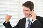 Smiling businessman using mobile phone while clenching fist — Stock Photo