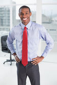 Elegant smiling Afro businessman standing in office — Stock Photo