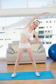 Sporty woman stretching body in fitness center — Stock Photo
