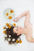 Belle femme couchée avec bol de fleurs dans un salon de beauté — Photo