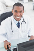 Smiling doctor using computer at medical office — Stock Photo