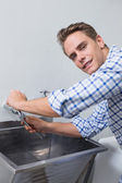 Portrait of plumber fixing water tap with pliers — Stock Photo