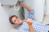 Plumber repairing washbasin drain while gesturing thumbs up — 图库照片