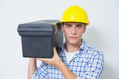 Serious handyman in yellow hard hat carrying toolbox — Stock Photo