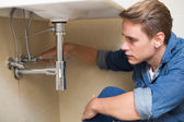 Handsome plumber repairing washbasin drain in bathroom — Stock fotografie