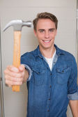 Smiling young handyman holding out hammer — Stock Photo