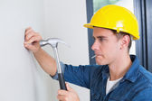 Handyman hammering nail in wall — Stock Photo