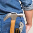 Several tools in a man's rear denim pocket — Stock Photo