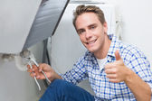 Plumber repairing washbasin drain while gesturing thumbs up — Stok fotoğraf