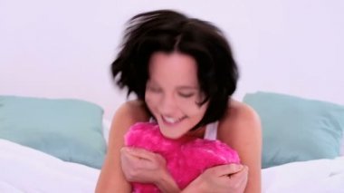Lovely cheerful woman cuddling with heart pillow — Stock Video