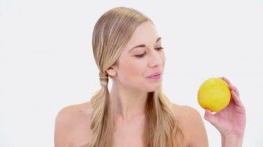 Happy nude blonde holding orange — Stock Video