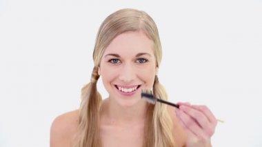 Happy nude blonde using eyebrow brush — Stock Video
