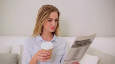 Calm blonde woman reading newspaper sitting on couch — Stock Video