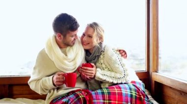 Cute couple relaxing together under a blanket in their ski lodge — Stock Video