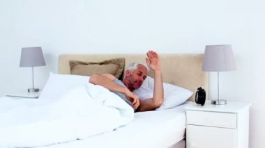 Refreshed man waking up and looking at his alarm clock — Stock Video