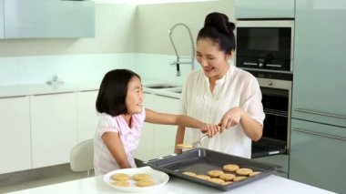 Mother and daughter taking cookies from baking tray — Stock Video