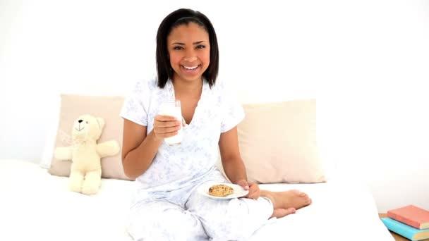 Linda mujer sentada sobre su cama bebiendo un vaso de agua — Vídeo de stock