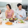 Young family of four enjoying healthy meal in kitchen — Stock Photo