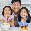 Smiling man with two daughters having breakfast in kitchen — Stock Photo