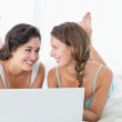 Happy relaxed female friends using laptop in bed — Stock Photo #37826245