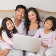 Happy relaxed family of four using laptop in bed — Stock Photo