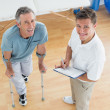 Stock Photo: Therapist and disabled patient with reports in gym hospital