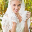 Beautiful blonde bride holding her veil smiling at camera — Stock Photo