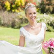 Beautiful blonde bride holding bouquet and her dress smiling at camera — Stock Photo #37826793