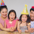 Stock Photo: Cheerful family of four playing with firecrackers