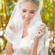 Beautiful blonde bride touching her veil and smiling — Stock Photo #37827231