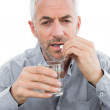Close-up of a mature man with glass of water and pill — Stock Photo