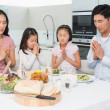 Family of four saying grace before meal in kitchen — Stock Photo