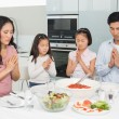 Family of four saying grace before meal in kitchen — Stock Photo #37827755