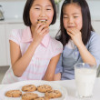 Two smiling girls enjoying cookies and milk in kitchen — Stock Photo #37828105