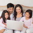 Relaxed family of four using laptop in bed — Stock Photo