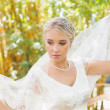 Calm blonde bride holding her veil out — Stock Photo