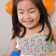 Cute girl looking at cake at her birthday party — Stock Photo #37828753