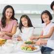 Happy family of four enjoying healthy meal in kitchen — Stock Photo