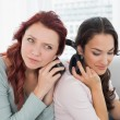 Stock Photo: Friends listening music through headphones together at home