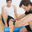 Stock Photo: Physical therapist examining young mans leg