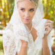 Beautiful blonde bride holding her veil — Stock Photo
