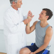 Male doctor examining a patients hand — Stock Photo