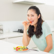 Young woman eating salad in the kitchen — Stock Photo #37829789