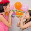 Stock Photo: Girls blowing noisemakers at birthday party