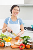 Smiling woman chopping vegetables in kitchen — Foto de Stock