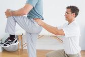 Therapist massaging mans lower back in gym hospital — ストック写真
