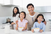 Family of four having breakfast in the kitchen — Stock Photo