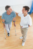 Therapist and disabled patient with reports in gym hospital — Stock Photo