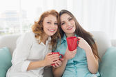 Female friends with coffee cups in the living room — Stock Photo