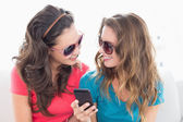 Female friends in sunglasses reading text message — Stock Photo